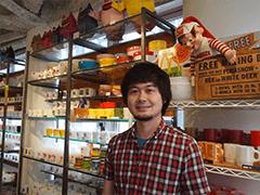 「DEALERSHIP」オーナーの井川雄太さん。店内にはマグやプレートなど食器のほか、アドバタイジング用のキャラクターグッズも。